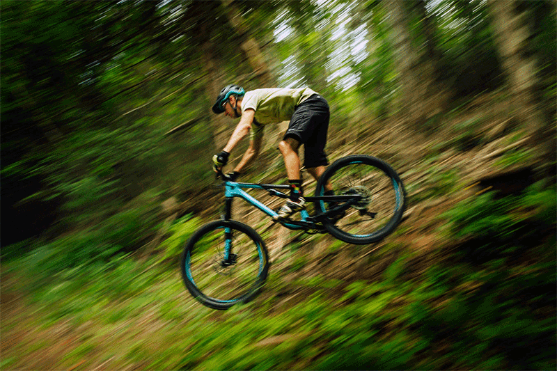person riding an enduro bicycle down the hill